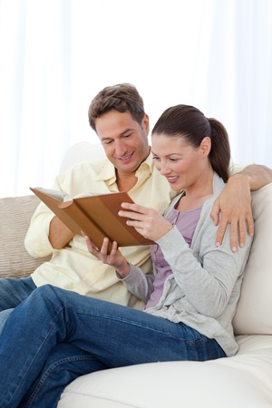 Happy couple looking at pictures on a picture album while relaxing Stock Photo - 10172313