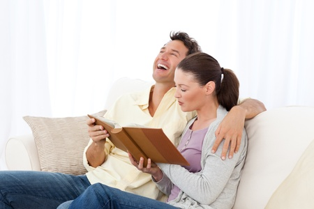 Man laughing while looking at a photo album with his girlfriend Stock Photo - 10170460