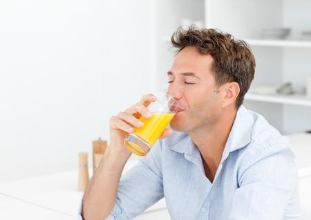 jus orange glazen: Knappe man genieten van zijn jus d'orange zat in de keuken Stockfoto