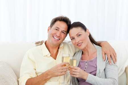 Portrait of a couple holding flutes of champagne on the sofa photo