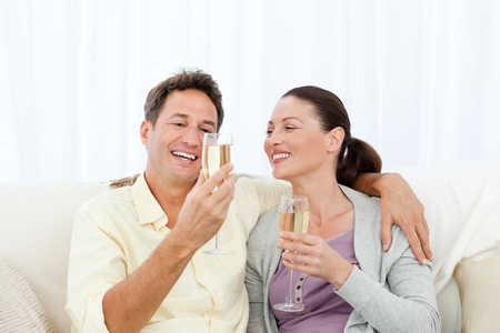 Happy couple tasting champagne sitting on the sofa photo