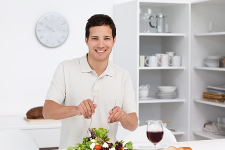 Happy man preparing a salad while drinking red wine Stock Photo - 10170410
