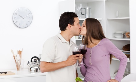 Cute couple kissing with glasses of red wine in their hands Stock Photo - 10212834