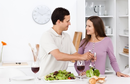 Attentive man serving salad to his girlfriend Stock Photo - 10206901