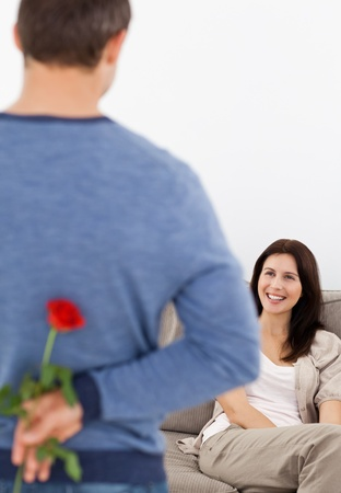 Enamored man hiding a flower behind his back for his girlfriend Stock Photo - 10217504