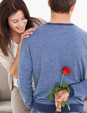 dar un regalo: Hombre atento ocultando una flor a la espalda de su novia de impaciencia
