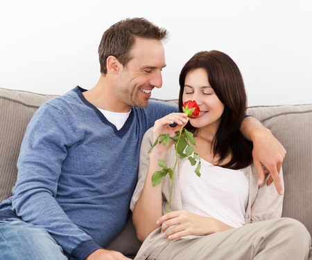 Lovely man looking at his girlfriend smelling a red rose Stock Photo - 10219301