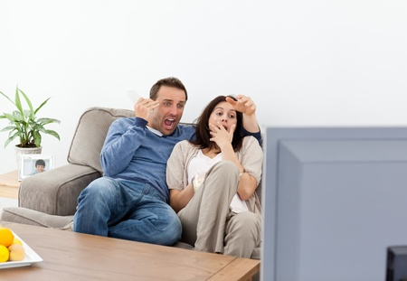 Scared couple watching a horror movie on the television photo
