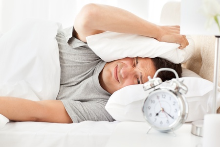 waking: Stressed man looking at his alarm clock ringing  Stock Photo