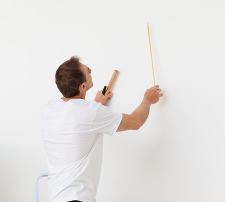 Handsome man looking at a wall with ruler and tools photo