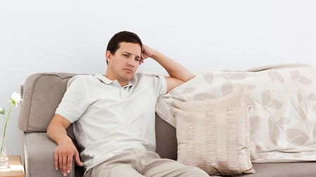 unsatisfactory: Depressed man thinking on the sofa