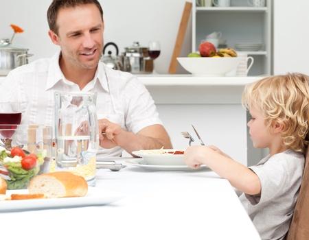 Happy dad looking at his son eating pasta photo