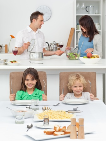 Brother and sister playing with forks while their parents cooking photo