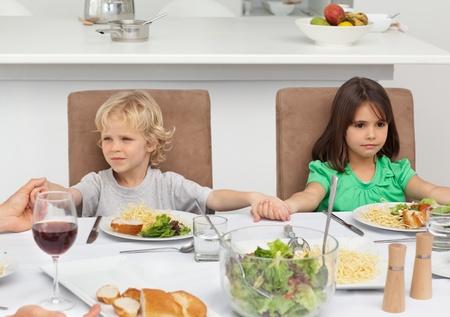 MaÅ'y brat i siostra posiadajÄ…cy swe rÄ™ce jednoczeÅ›nie praying w trakcie obiadu Zdjęcie Seryjne