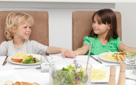Cute brother and sister holding their hands before lunch photo
