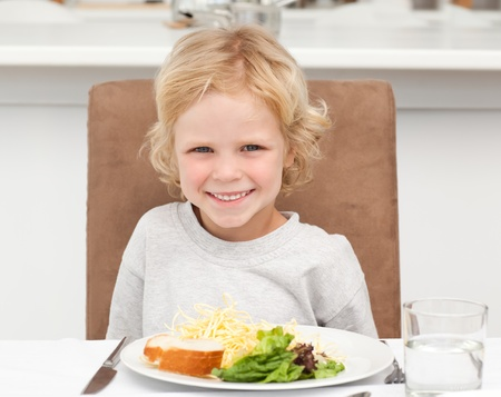 Cute little boy eating pasta and salad  photo