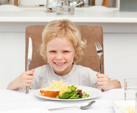 woman eat: Excited boy holding forks to eat pasta and salad
