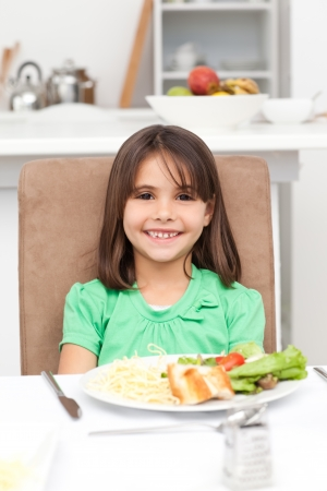 eating pasta: Cute little girl eating pasta and salad Stock Photo