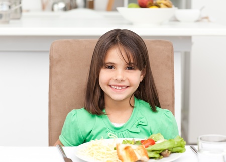 Portrait of a little girl eating pasta and salad photo