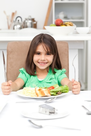 Adorable llittle girl holding forks to eat pasta and salad photo