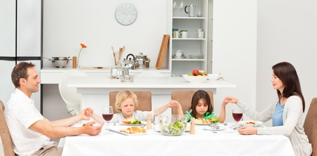 having lunch: Concentrated family praying before having lunch  Stock Photo