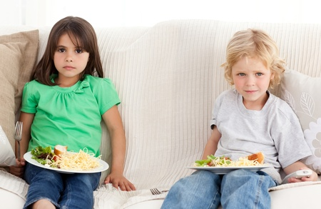 Serious brother and sister having dinner on the sofa  photo