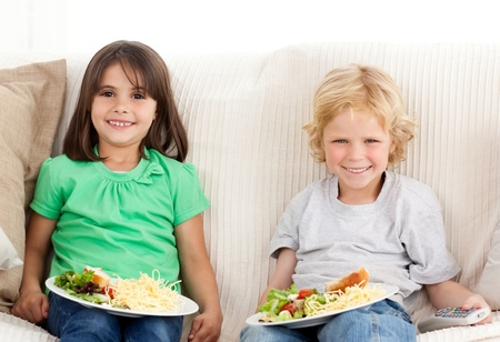 Happy brother and sister having TV dinner photo