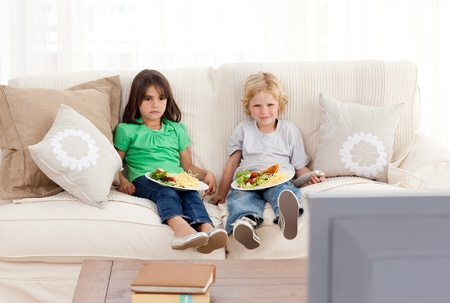 Cute brother and sister having dinner on the sofa Stock Photo - 10217609