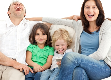 Family laughing while watching television together photo