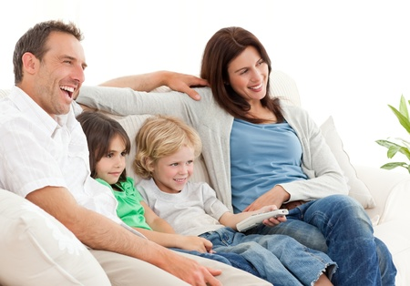 watching tv: Happy family watching television together