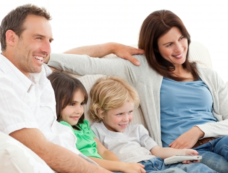 Parents and children watching television together photo