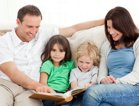 family picture: Cute girl and her family looking at a photo album