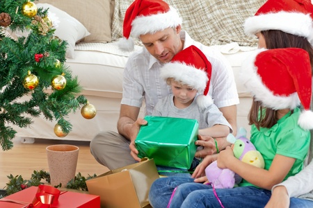 Happy family looking at the little boy opening a christmas present  photo