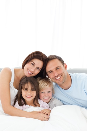 Portrait of a joyful family sitting on the bed Stock Photo - 10207139