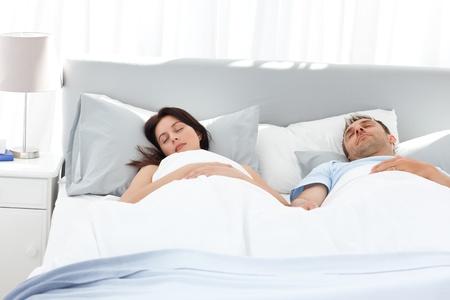 pareja durmiendo: Pareja encantadora su mano mientras dorm�a en su cama