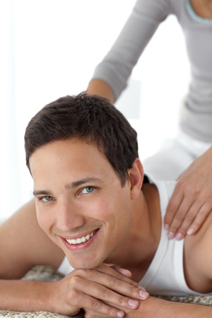 Cheerful man enjoying a back massage from his girlfriend on their bed photo