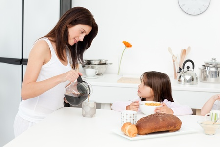 pajama: Pretty mom pouring coffee while her children having breakfast