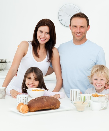 Portrait of a family having breakfast together in the kitchen photo