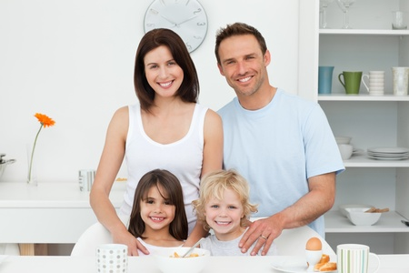 Enfants adorables posant avec leurs parents dans la cuisine