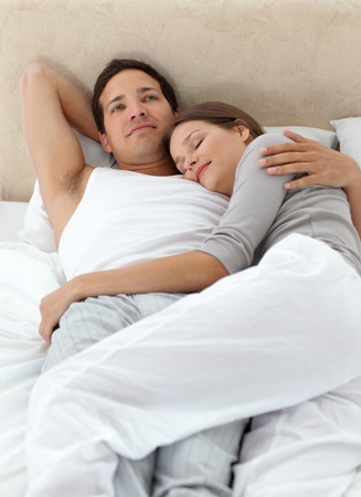 Peaceful man thinking while relaxing with his girlfriend