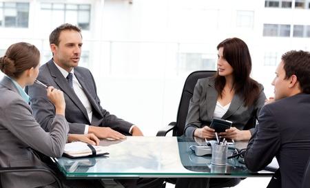 empleados trabajando: Carism�tico empresario hablando con sus compa�eros durante una reuni�n Foto de archivo