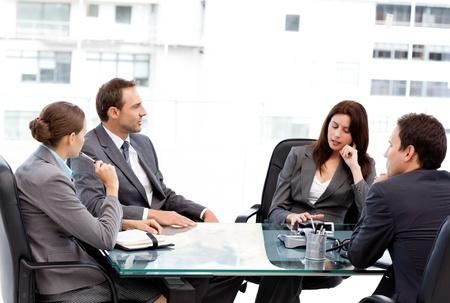 conferentie: Doordachte zakenvrouw in gesprek met haar team tijdens een vergadering Stockfoto