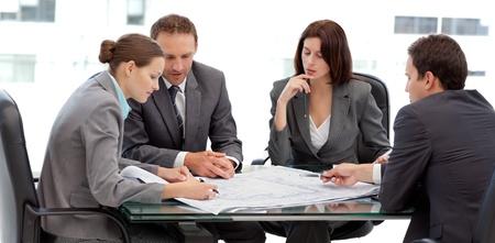 Vier schweren Ingenieure looking at Plans sitzen an einem Tisch