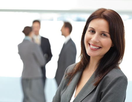 Pretty businesswoman posing in front of her team while working photo