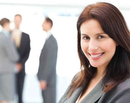 charisma: Charismatic businesswoman posing in front of her team