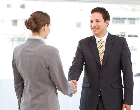 greet: Cheerful businessman and businesswoman concluding a deal