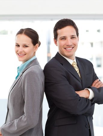 Happy businessman and businesswoman posing back to back photo