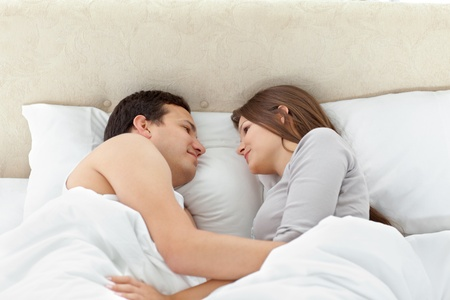 Tranquil couple looking at each other on their bed Stock Photo - 10220399