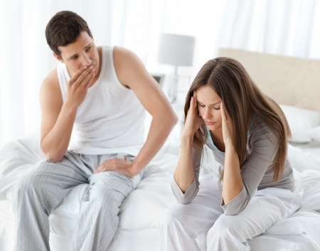 Worried man looking at his girlfriend having a headache on the bed Stock Photo - 10218870