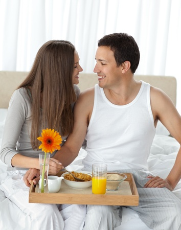 Passionate couple with their breakfast sitting on the bed Stock Photo - 10218922